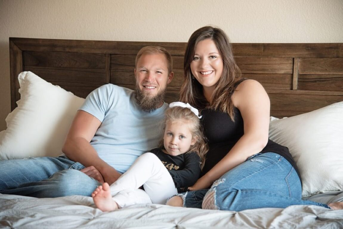 Photograph of family of 3 laying in bed