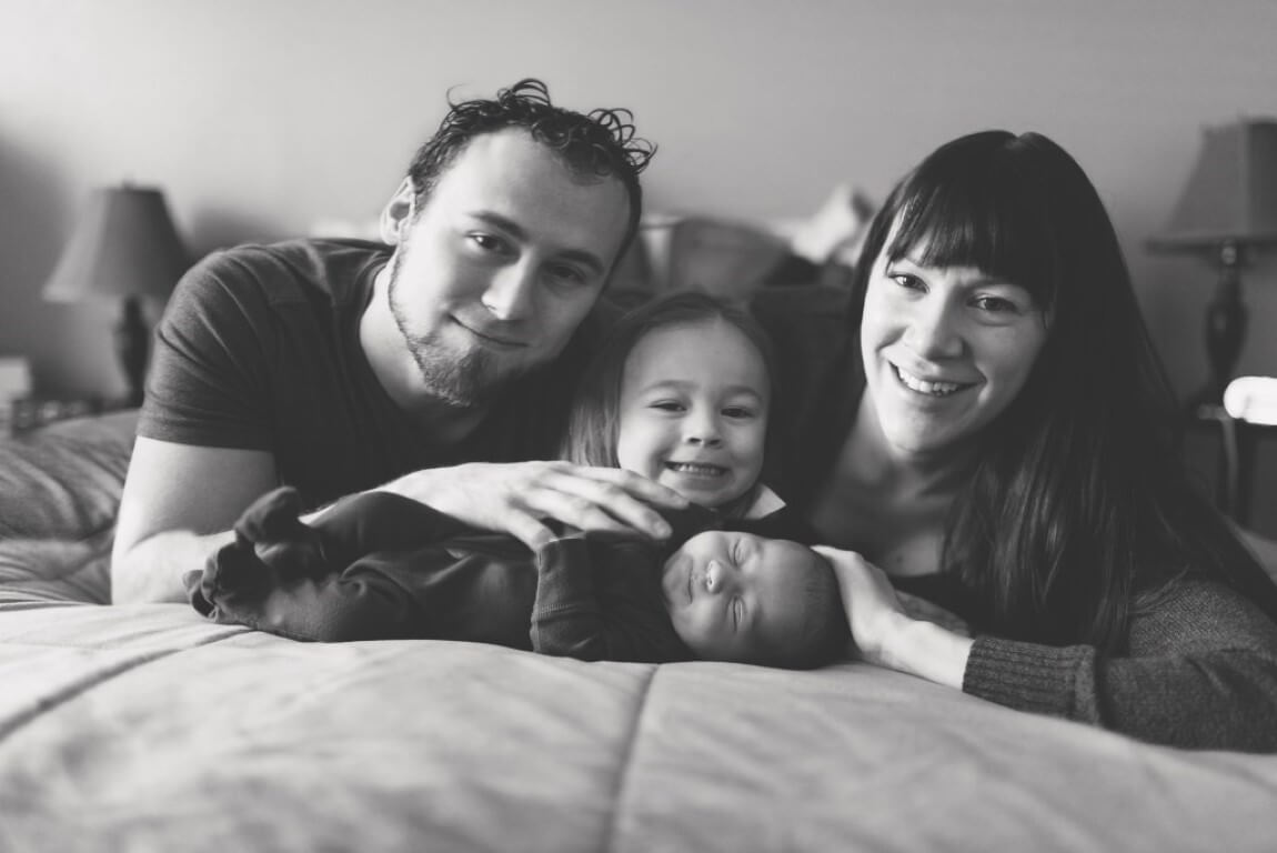 Family of 4 with baby laying in bed, black and white photo