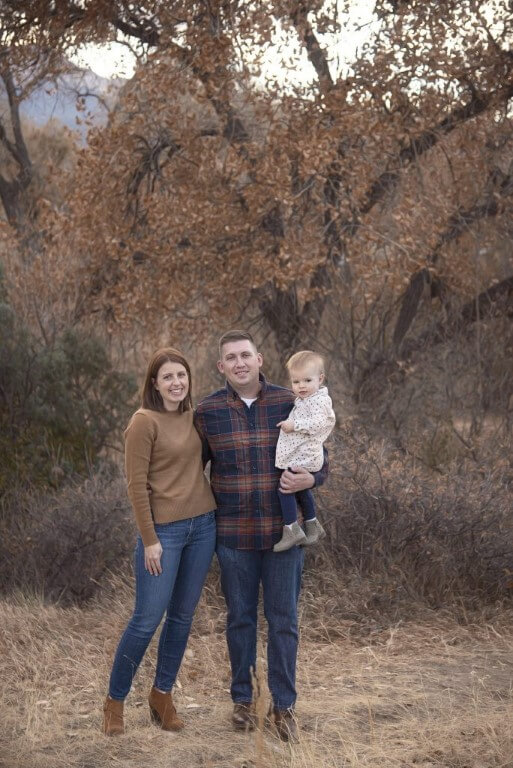 Photograph of family of 3 with baby against tree background