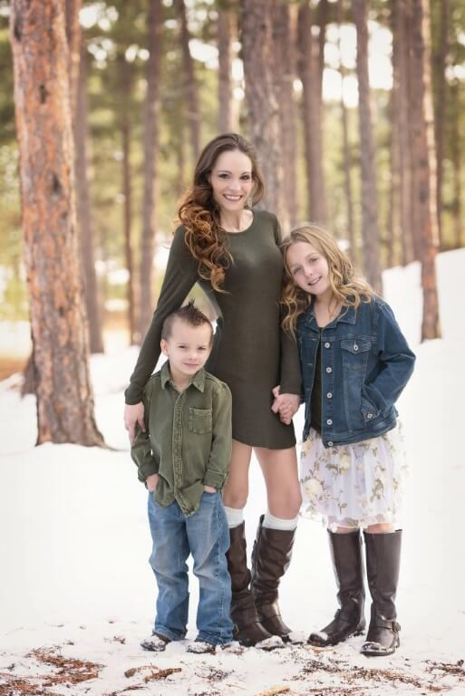 Photograph of family containing mom and two kids set against snowy forest background