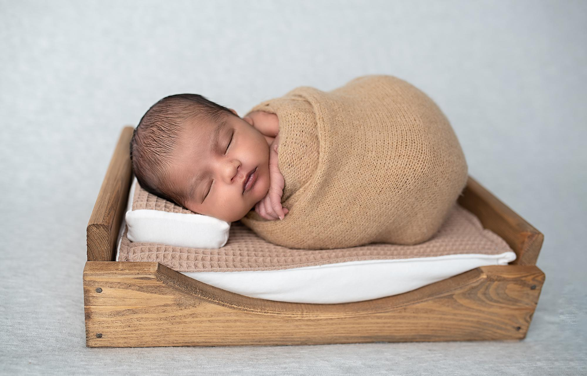 A newborn baby sleeping in a wooden bed