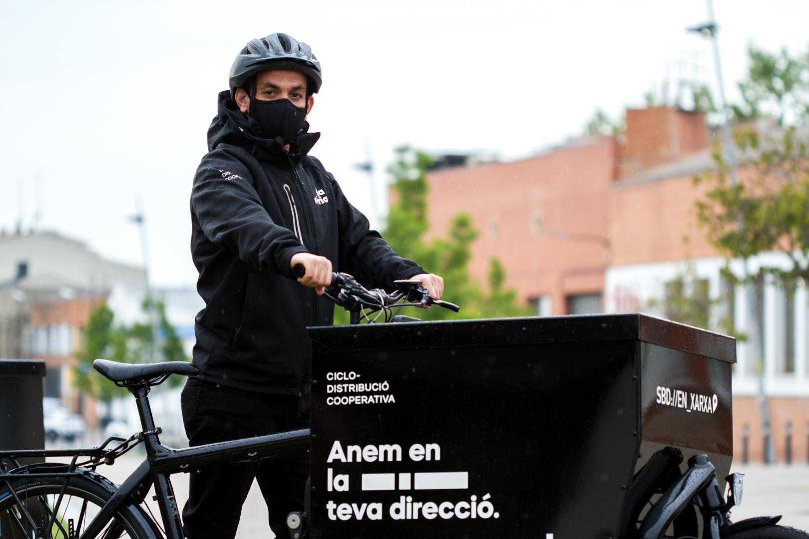 Foto d'un treballador de La Sàrria en bicicleta.