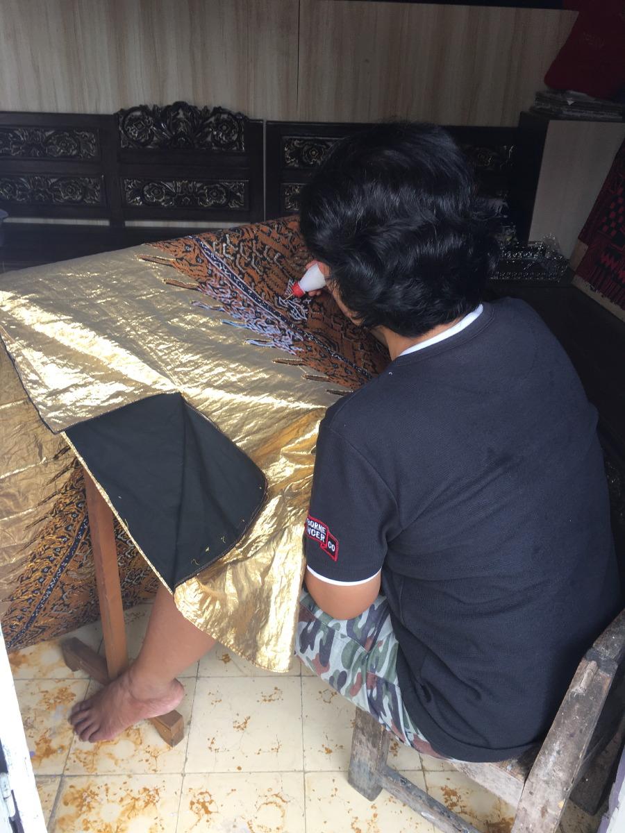 Batik crafting in an open doorway.