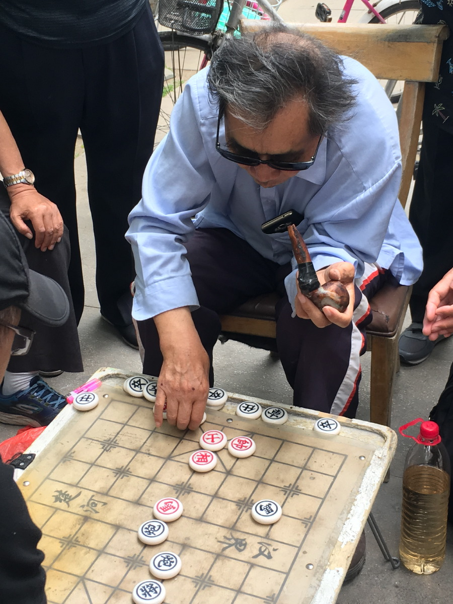 Hutong walks. Everywhere men are playing Chinese checkers.