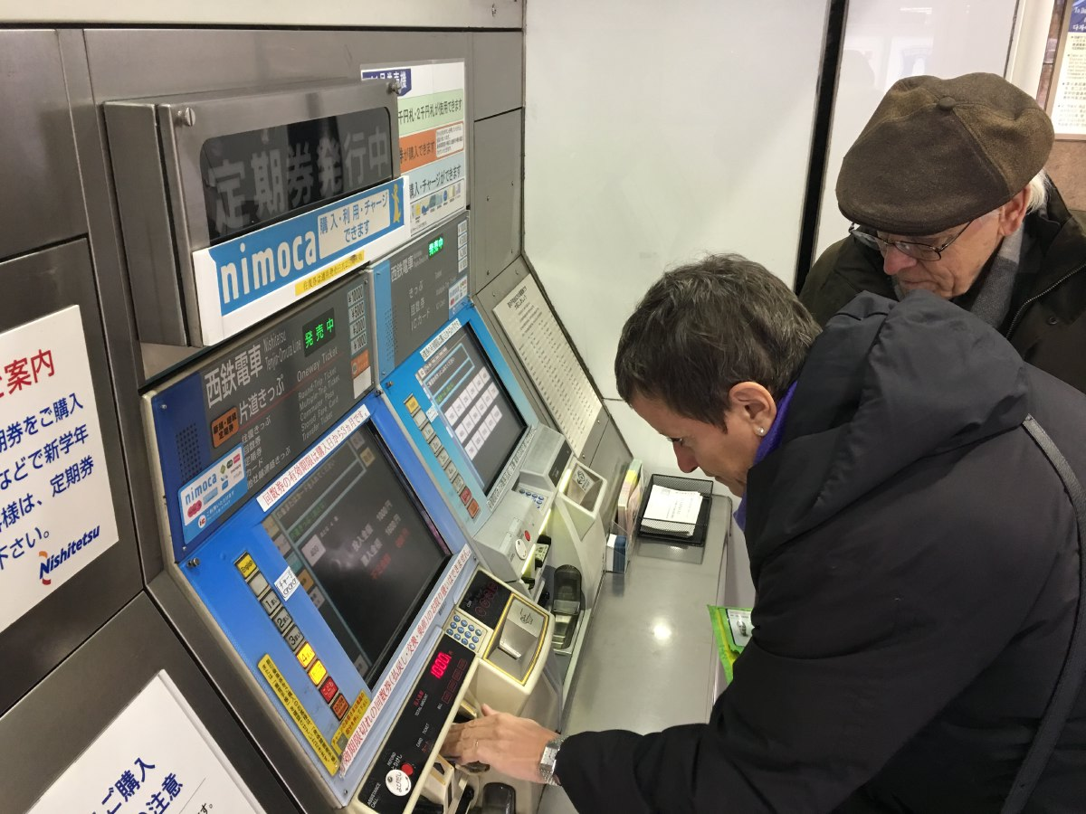 Taking the train. Vie finding her way around the ticketing machines at the Fukuoka railway station. There's no 'switch to English' button to be found so...