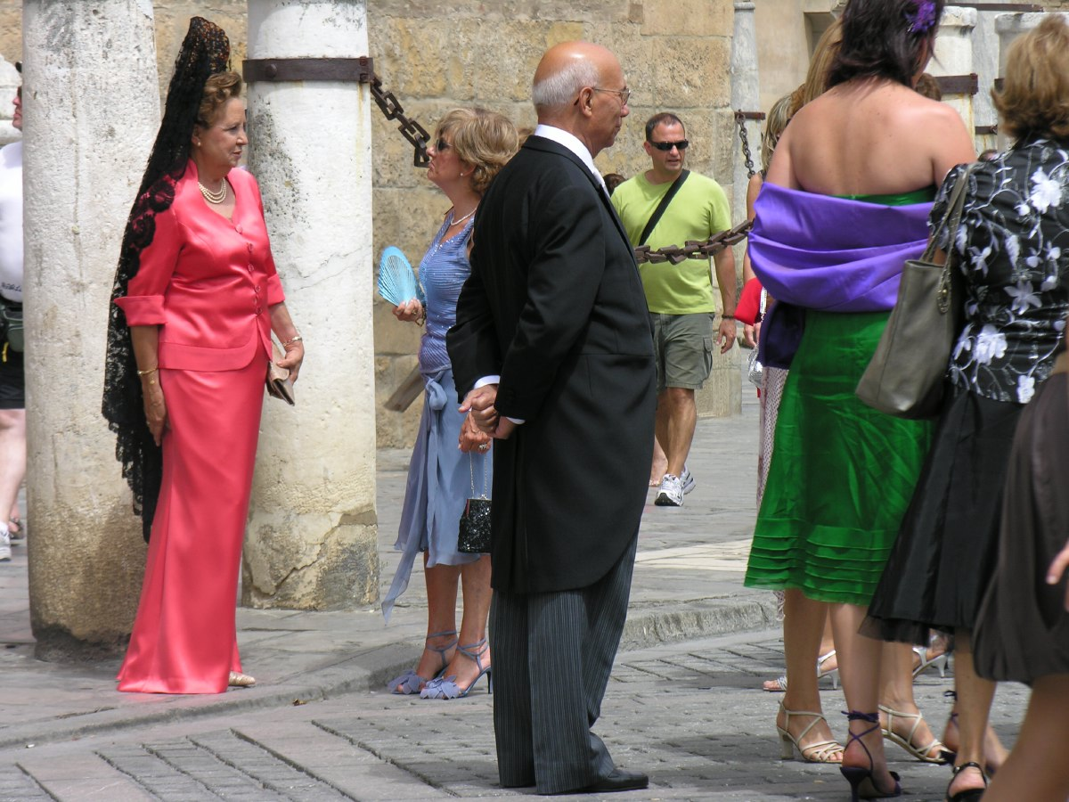As we approach the cathedral, the guests of a wedding party start to arrive. This is the mother of bride or groom...