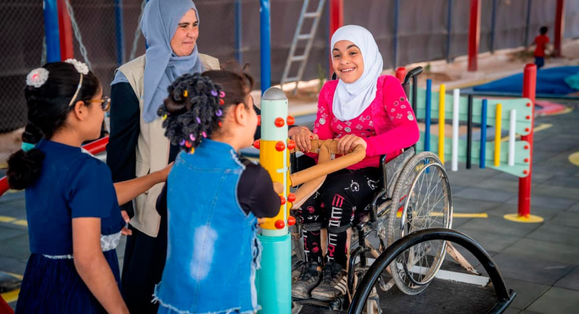 kids in a playground, with one kid in a hijab and using a wheelchair