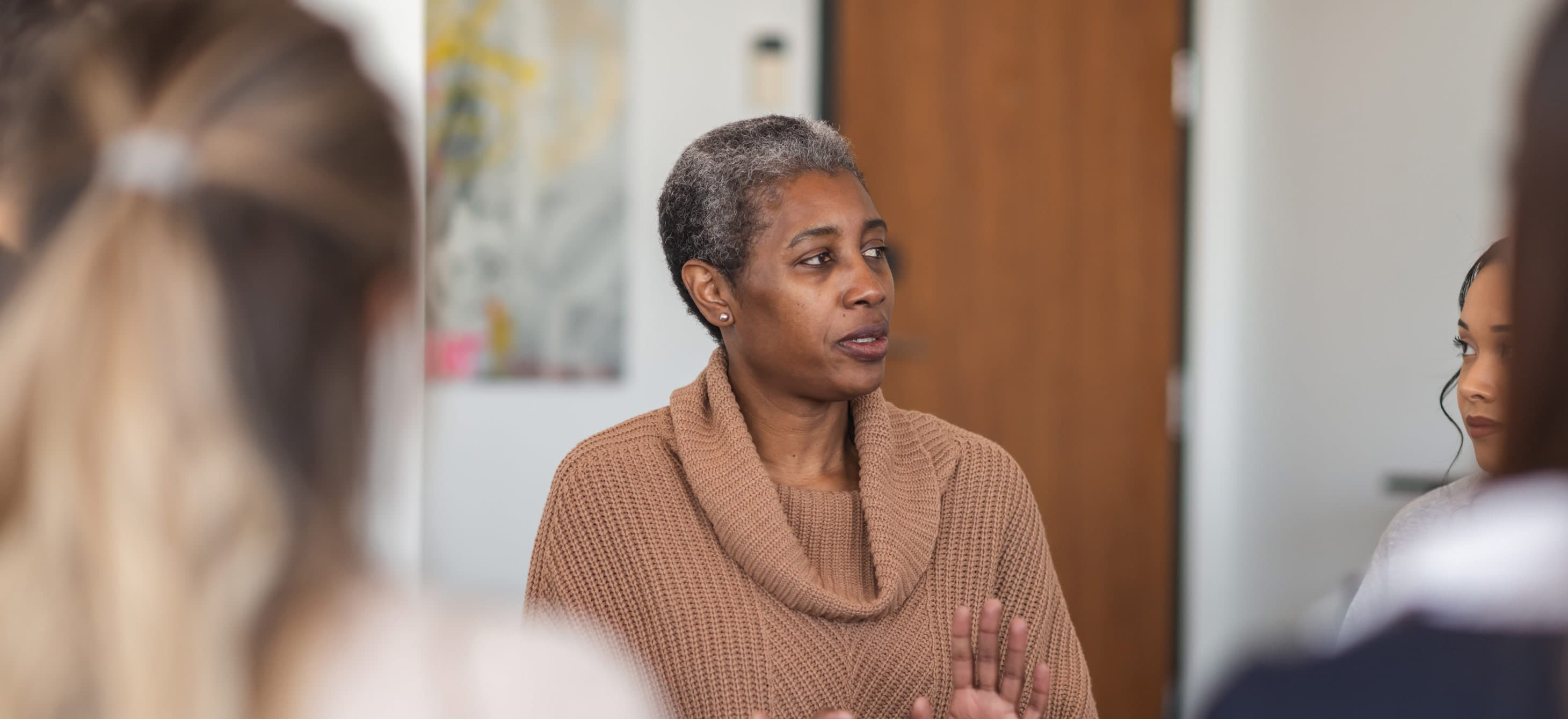 a Black woman leading a group meeting
