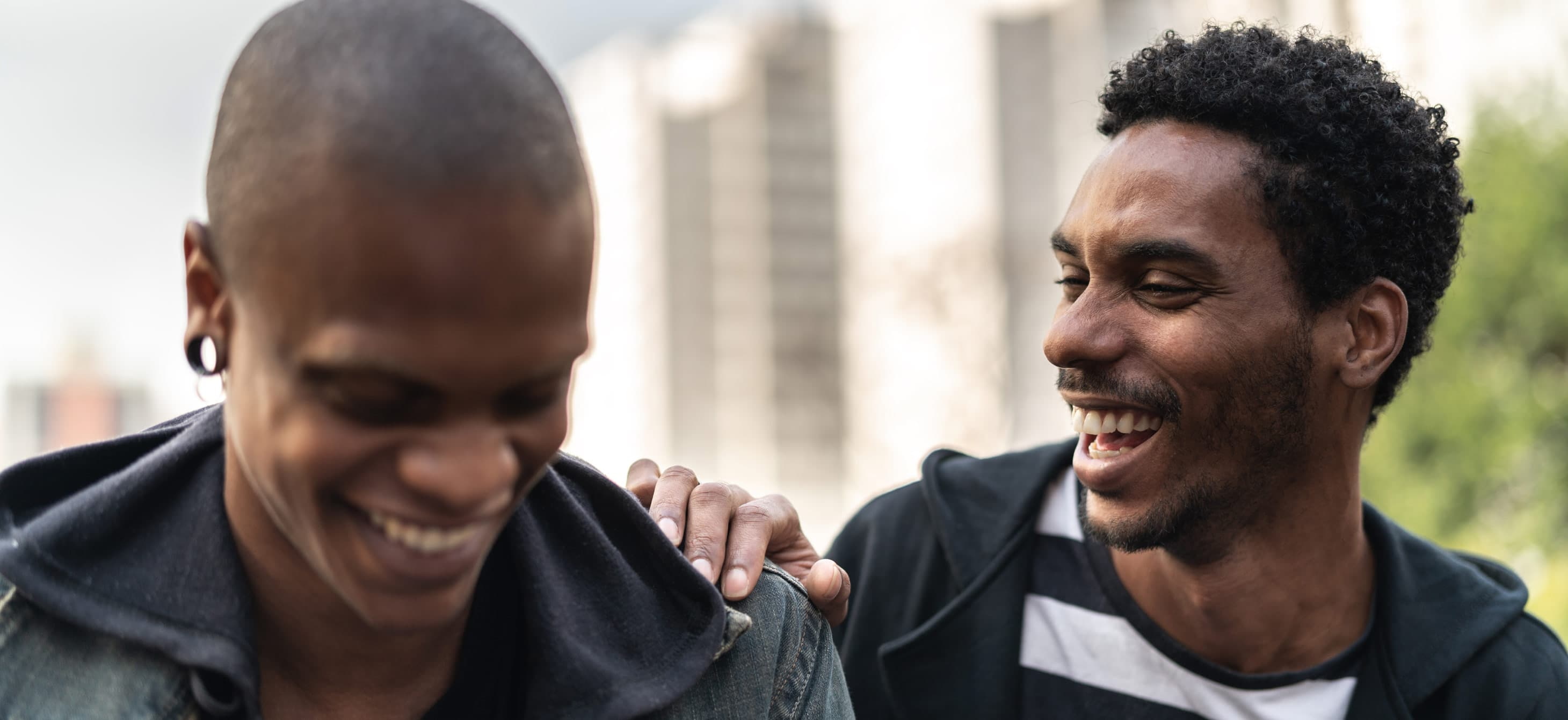 two Black men smiling at each other