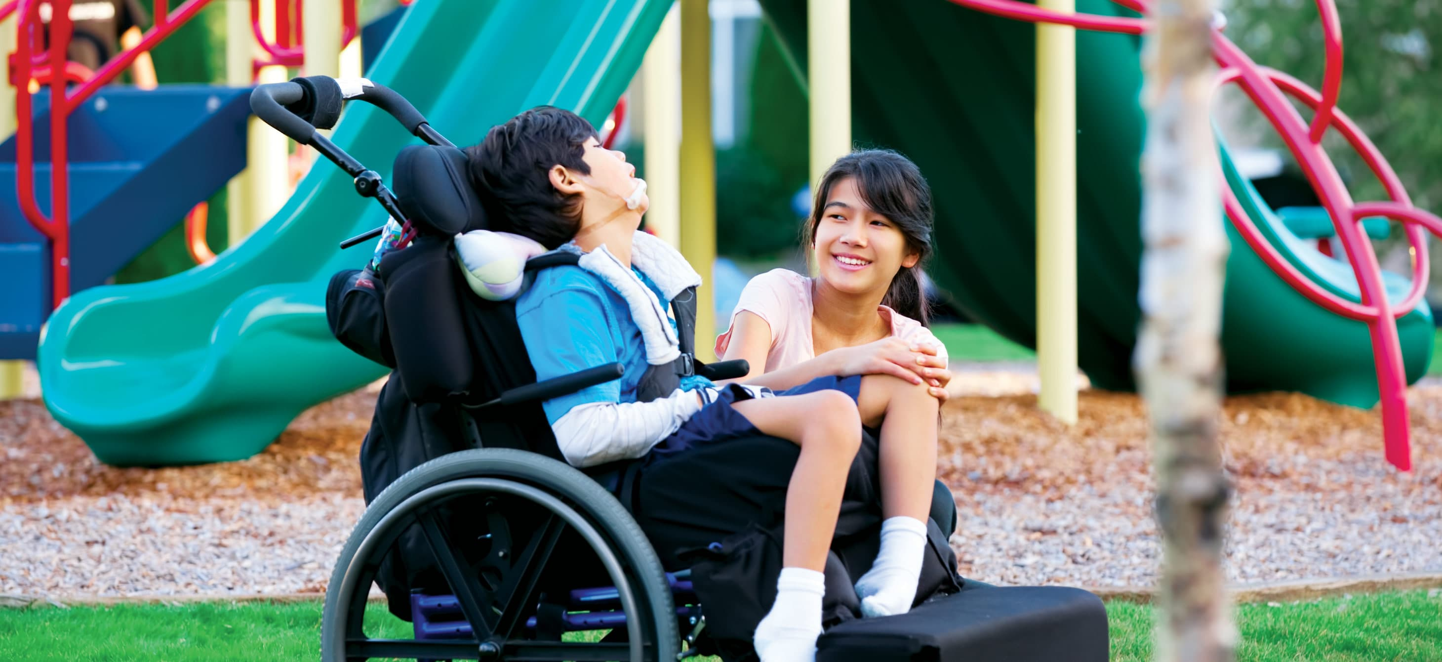 a child using a wheelchair and another child hanging out in a playground