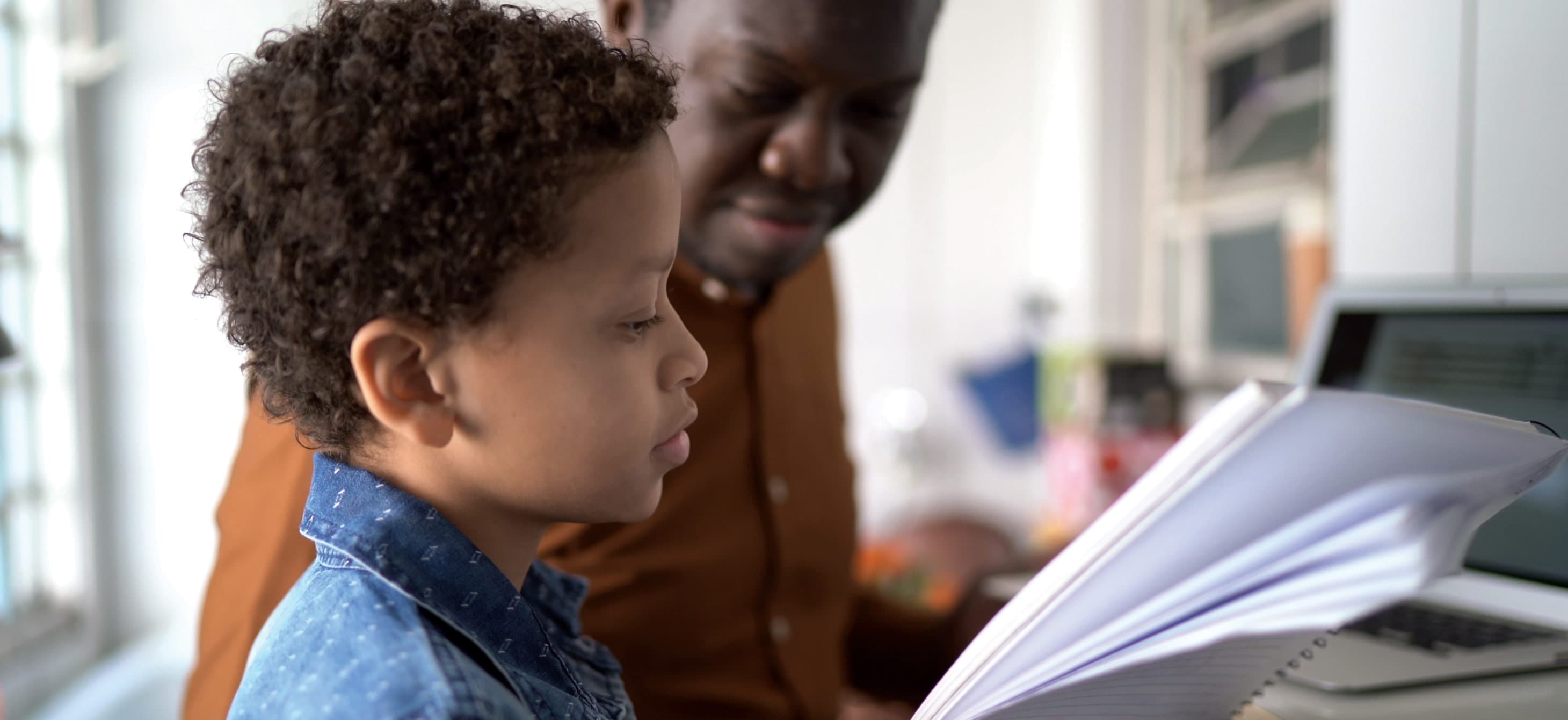a boy looking at a lined notebook with an adult next to him