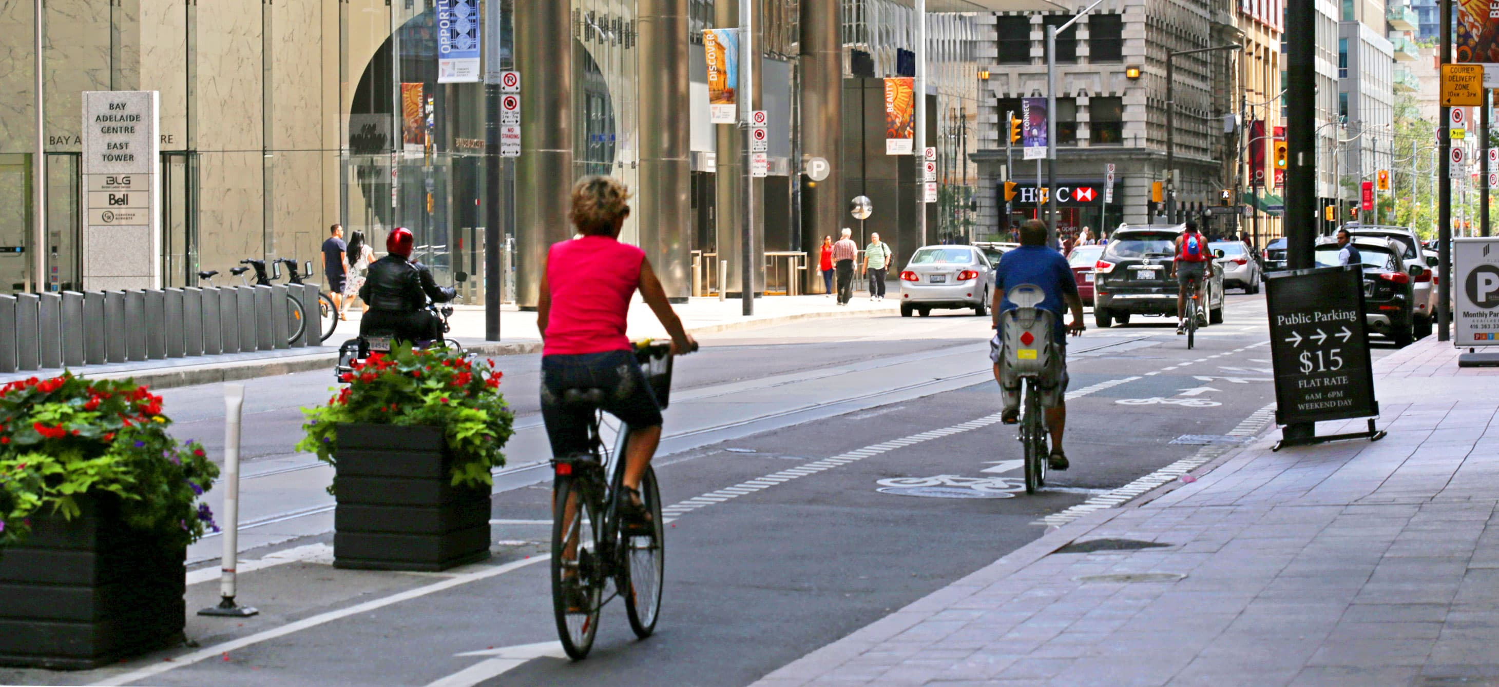 downtown street that has a sidewalk, a separated bike lane, and car lanes
