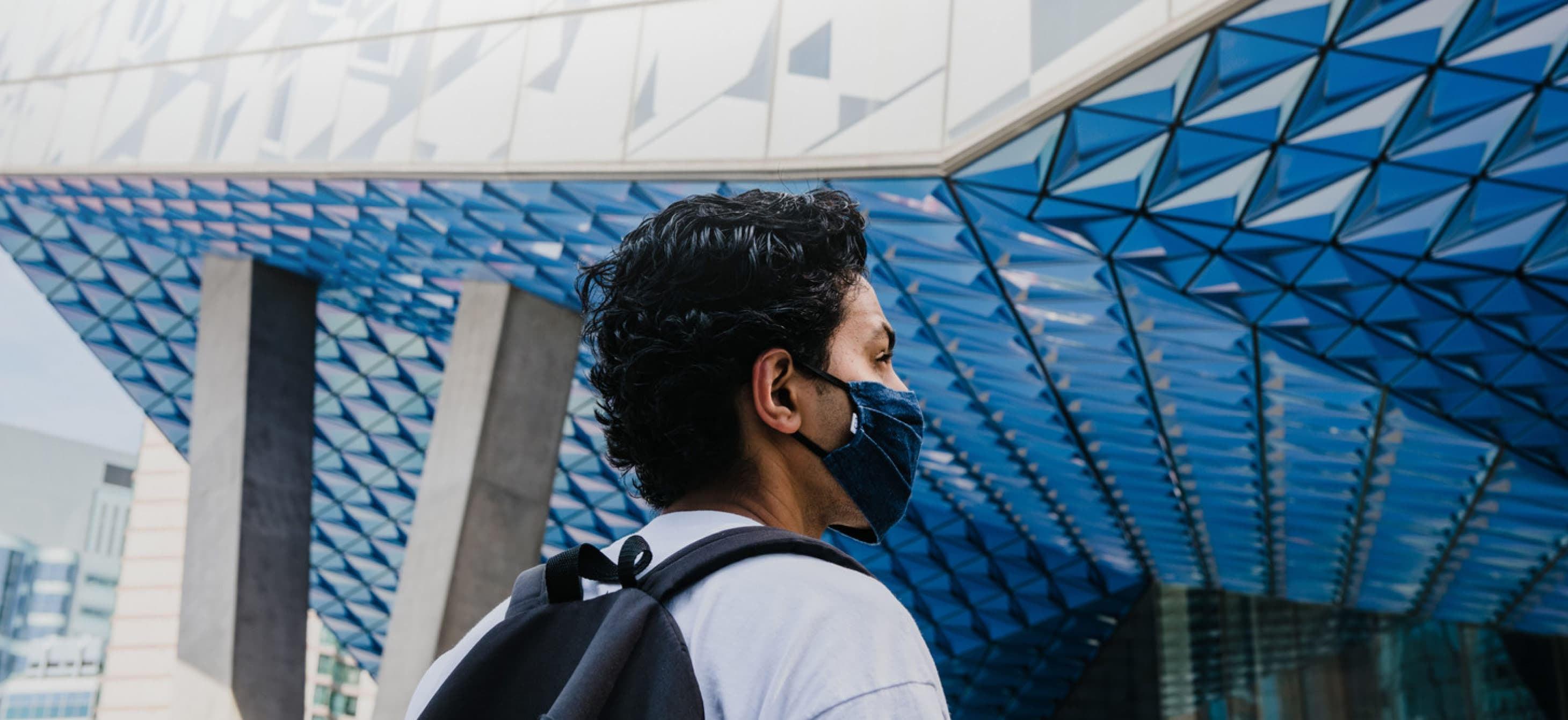 a student with a backpack and a mask in front of the Ryerson Student Learning Centre