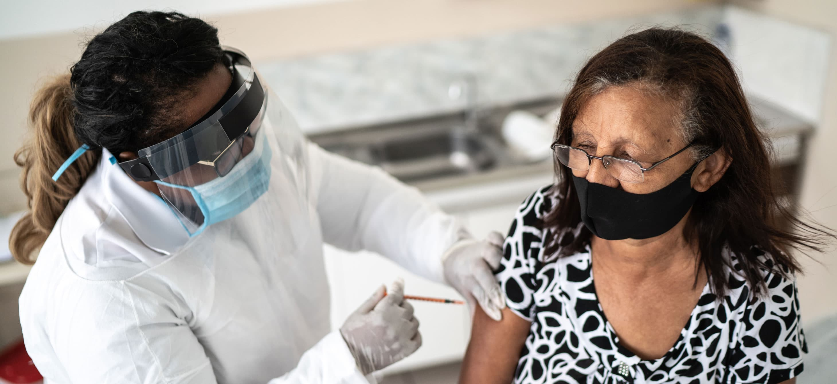 a nurse in PPE vaccinating an elderly woman wearing a mask