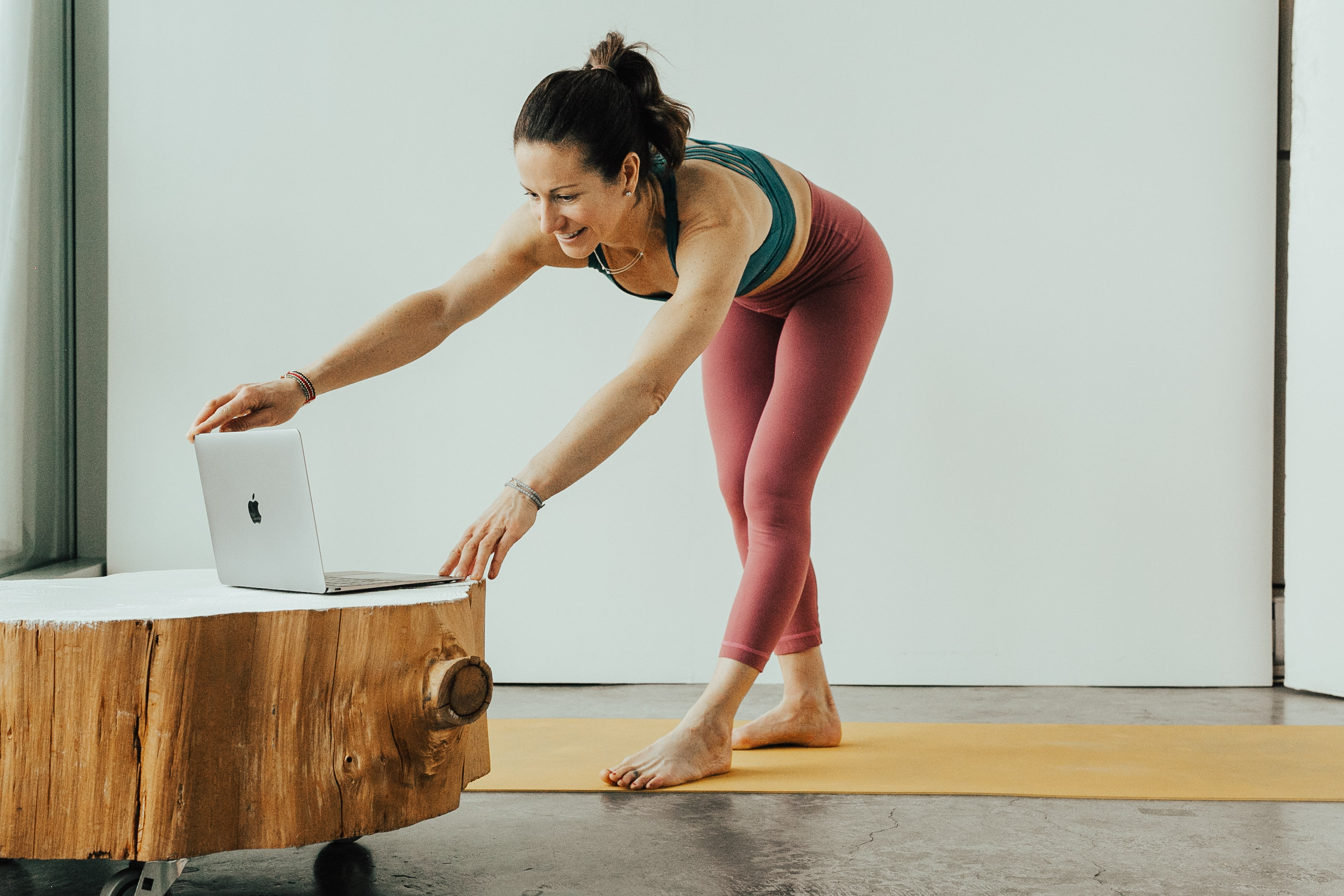 Woman doing online yoga from laptop