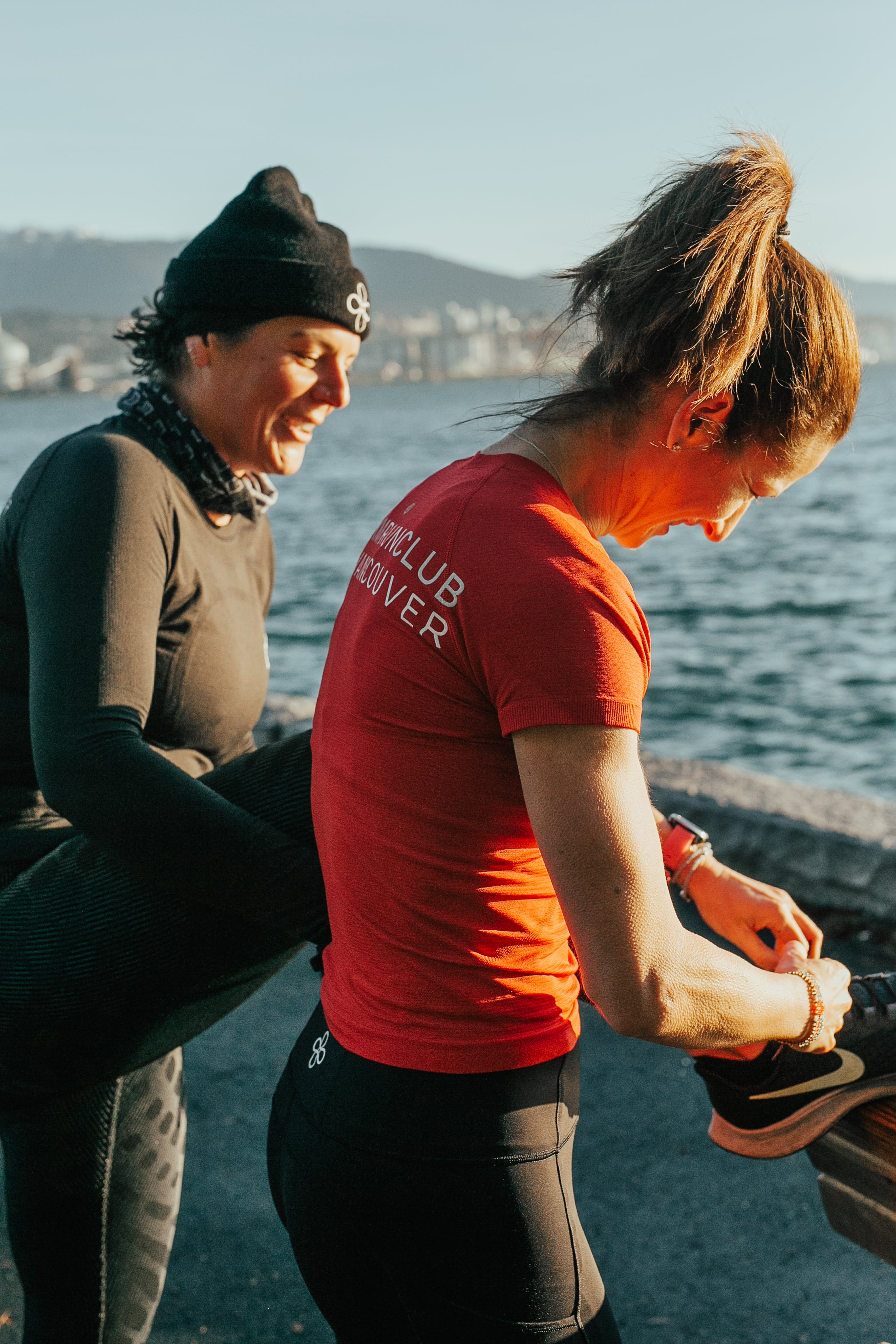 Woman helping tie another womans shoe
