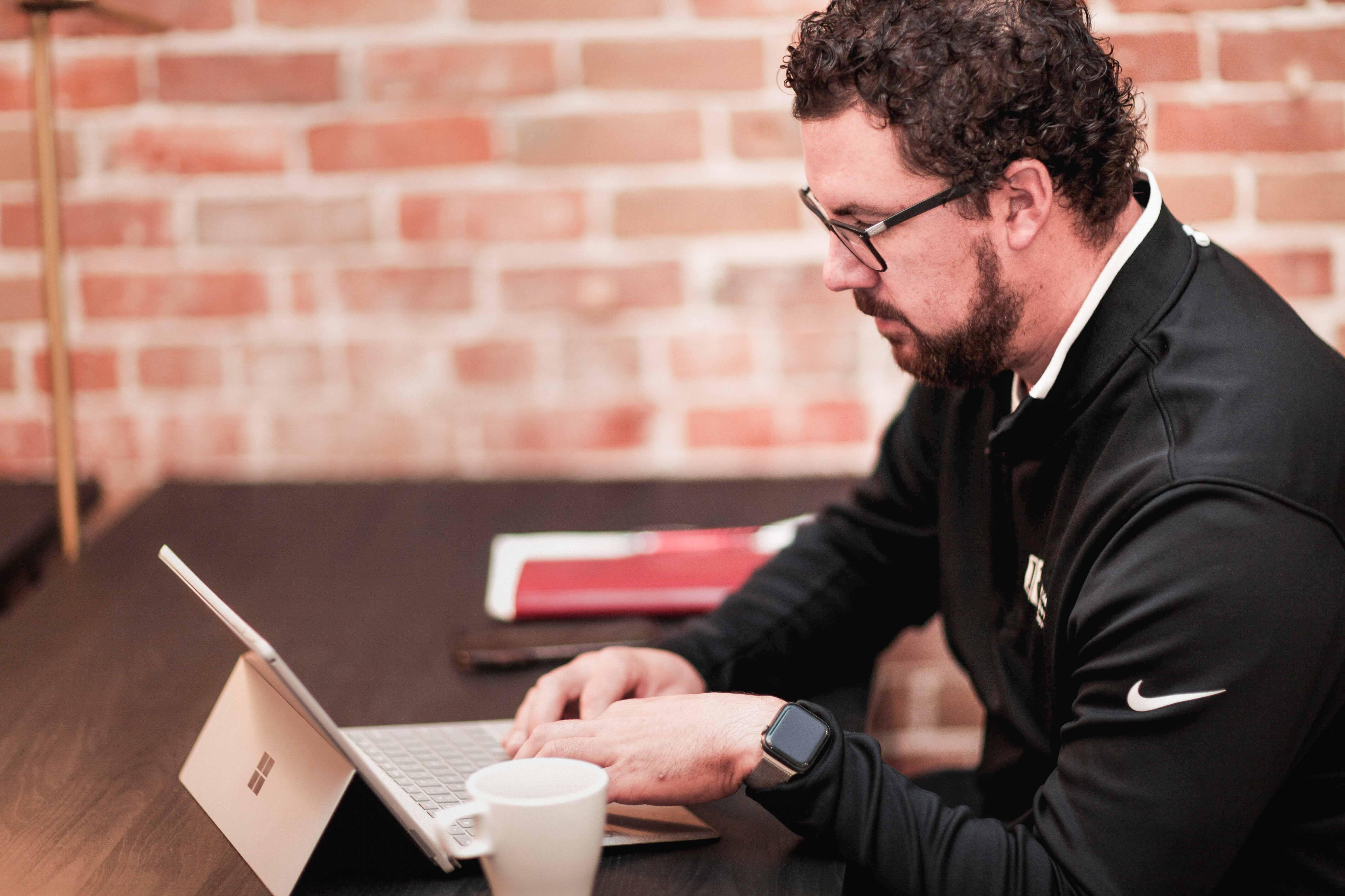 Man sitting at desk typing on a laptop