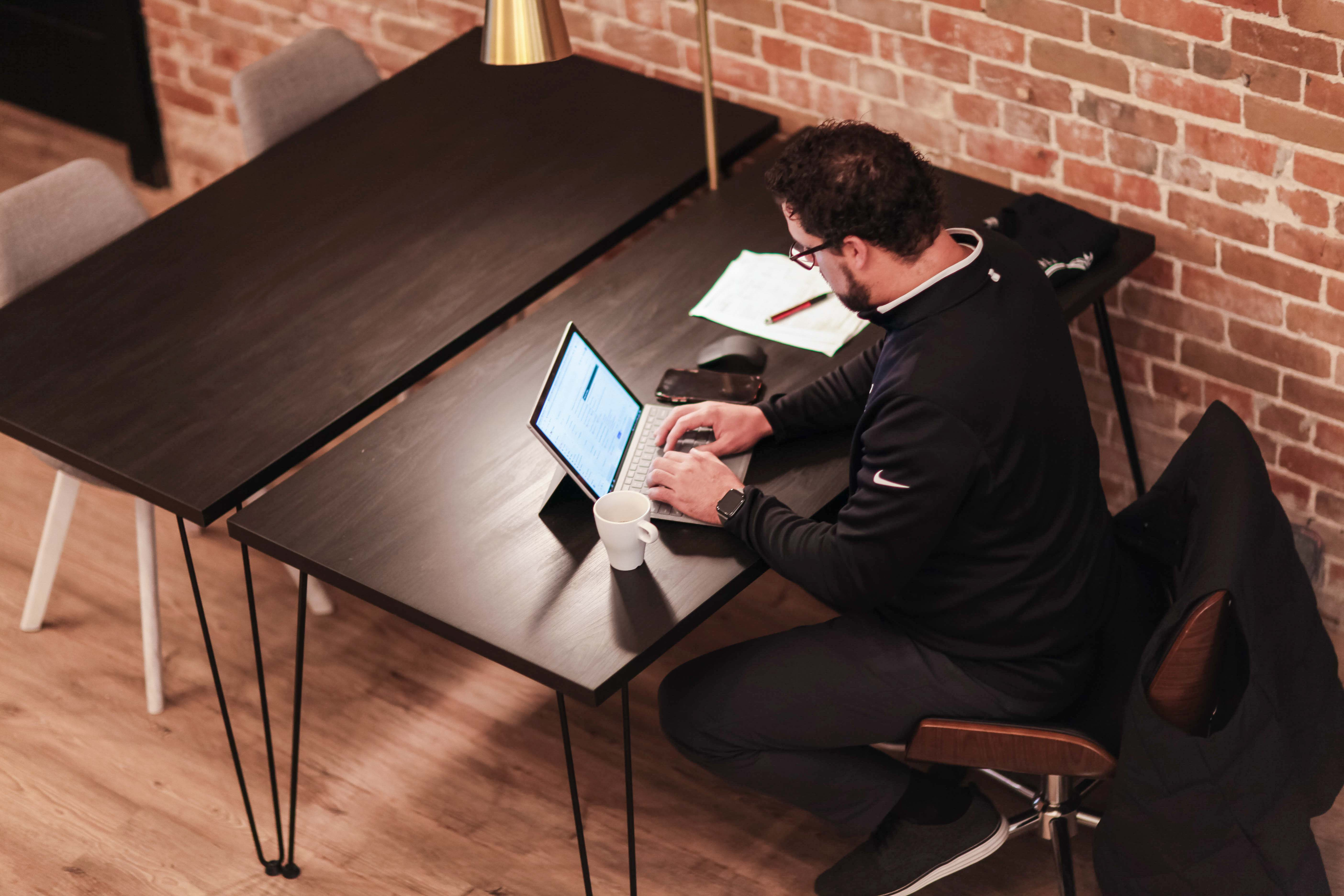 Person sitting at a desk working on a laptop