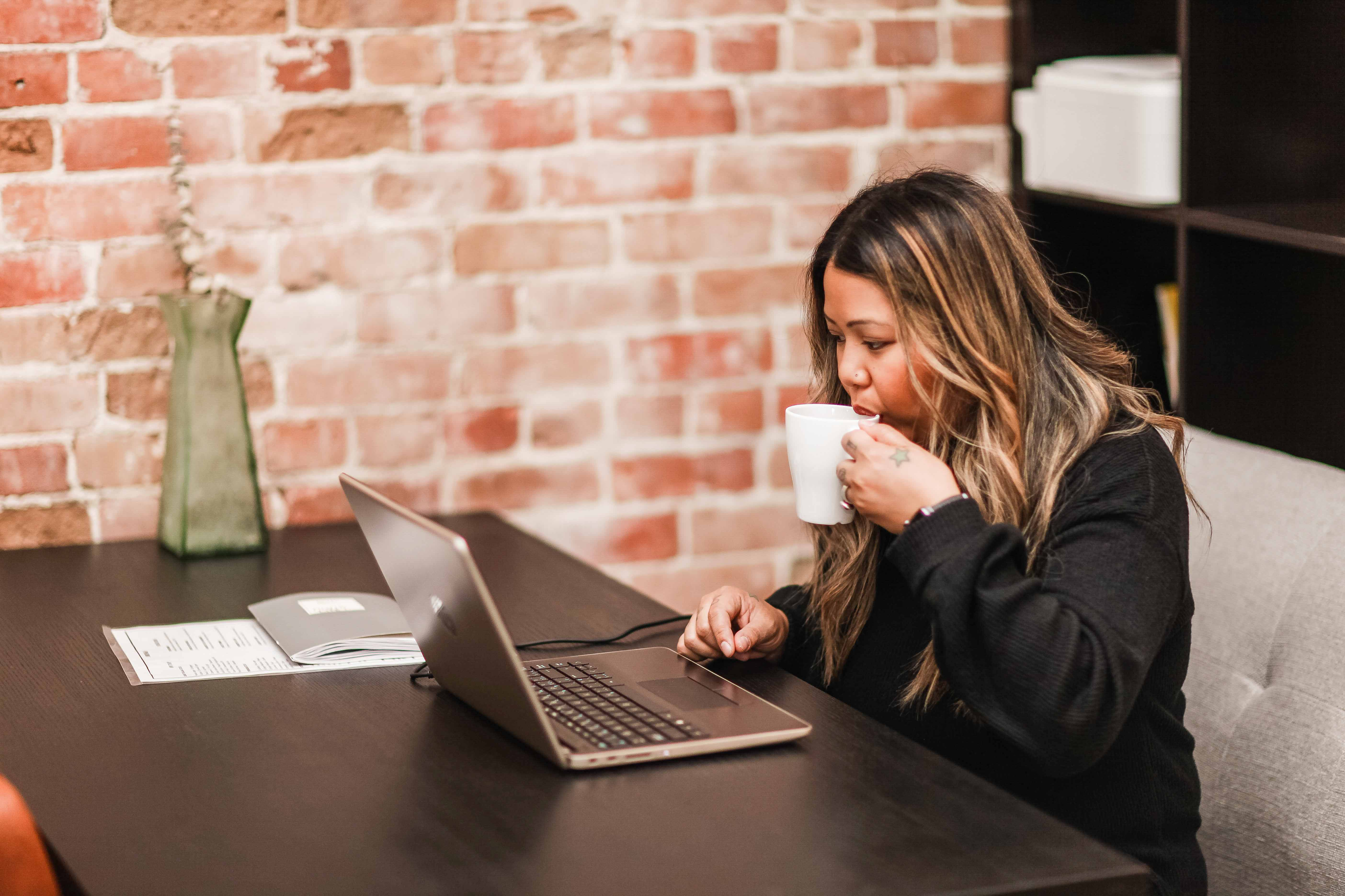 Person sipping on coffee working at a desk on a laptop