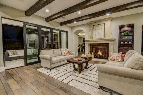 Living room with a fireplace and large sliding patio door in a custom built home