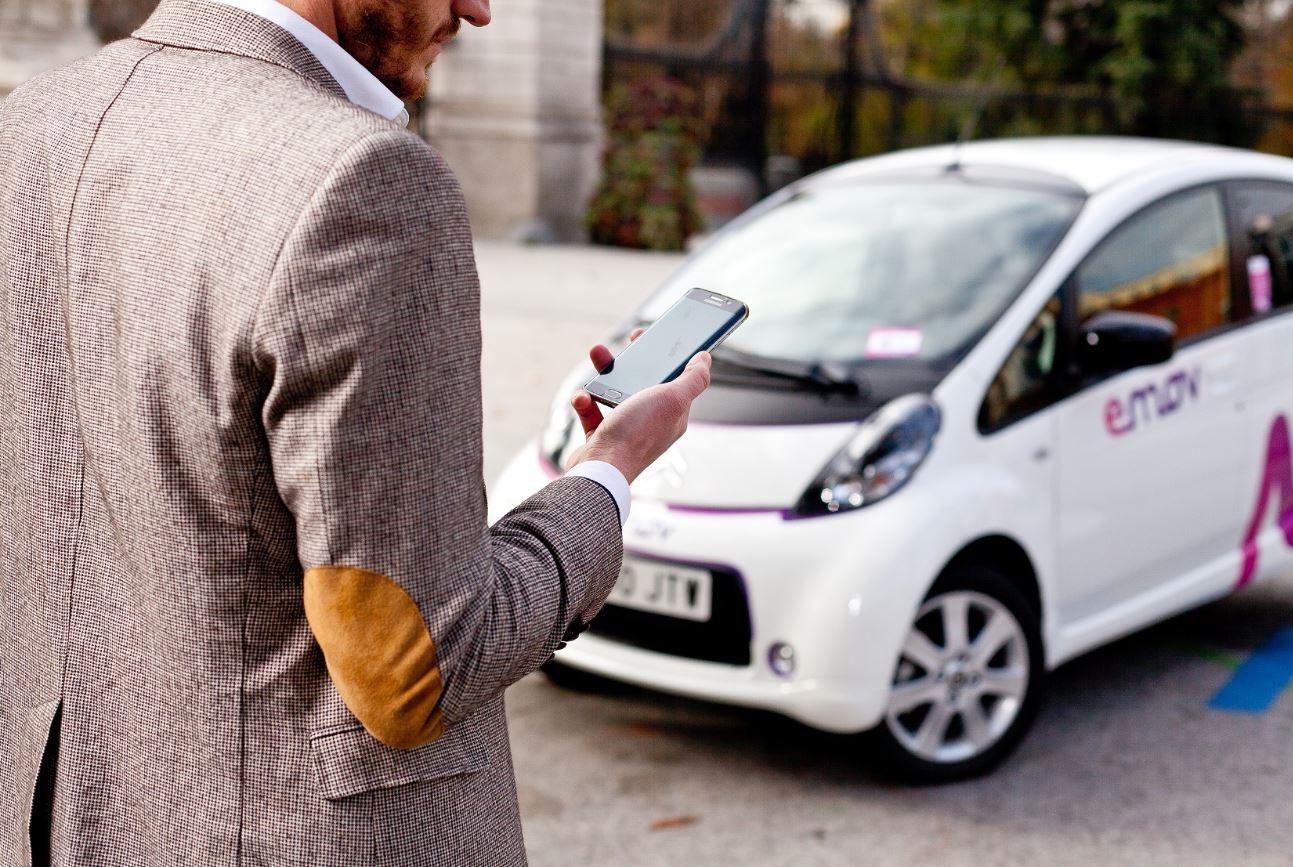 Una persona con móvil y un coche de Emov.