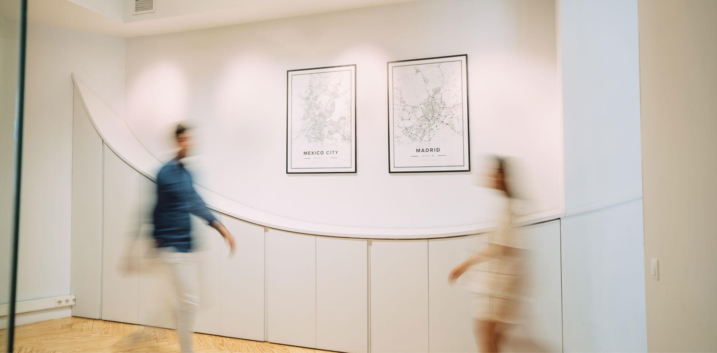 Dos figuras borrosas que caminan en la entrada de las oficinas.