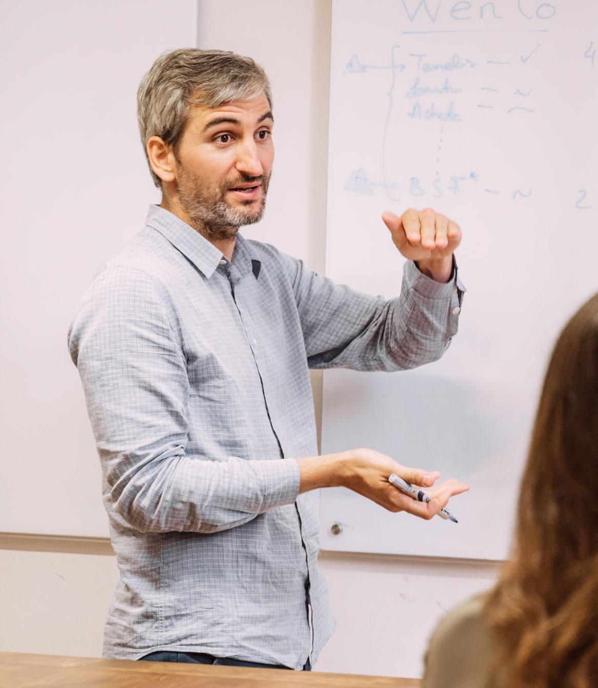 Una persona del equipo delante de la pizarra explicando conceptos a los demás.