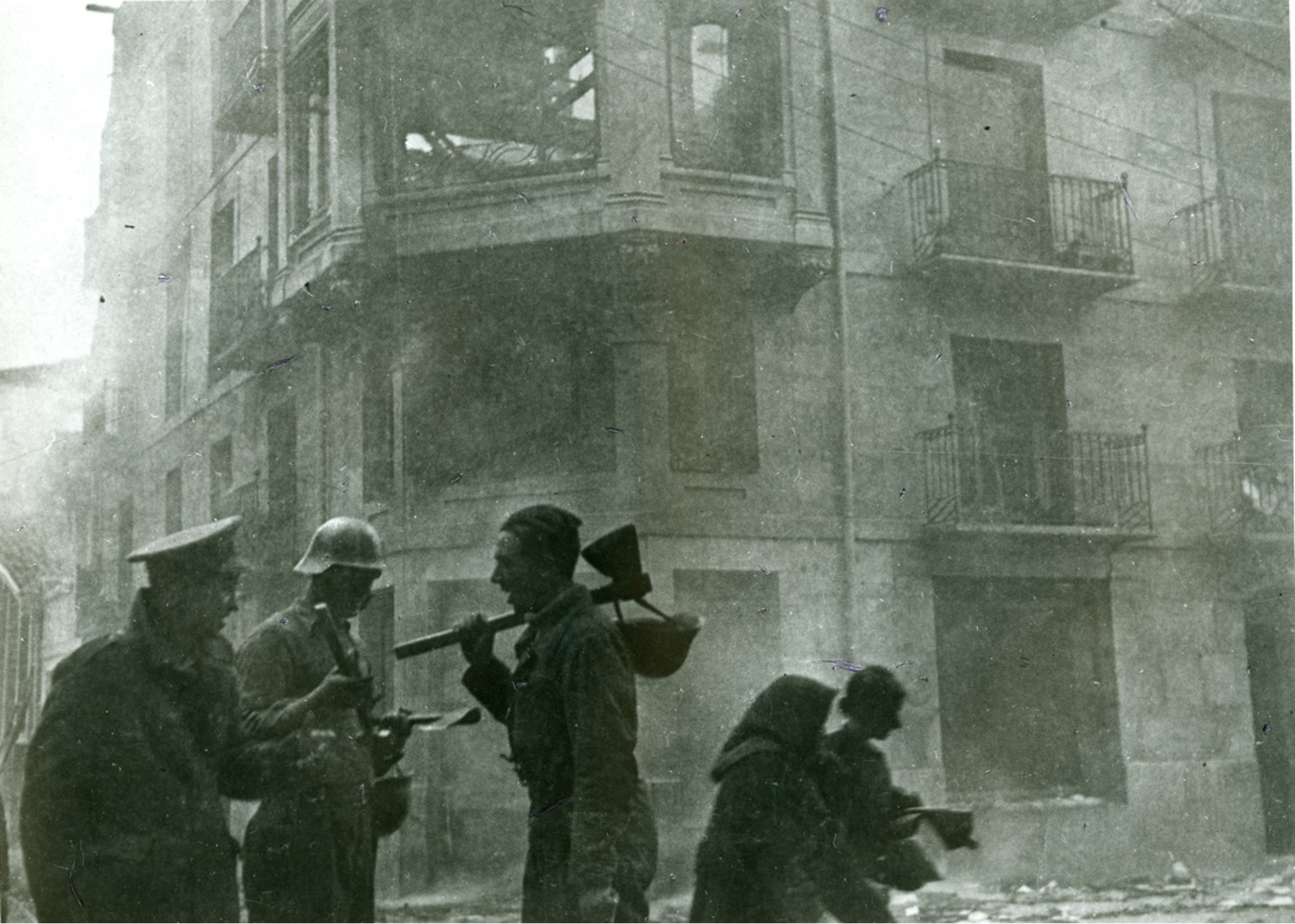 Civilians attempting to soft through rubble in Guernica, Spain.