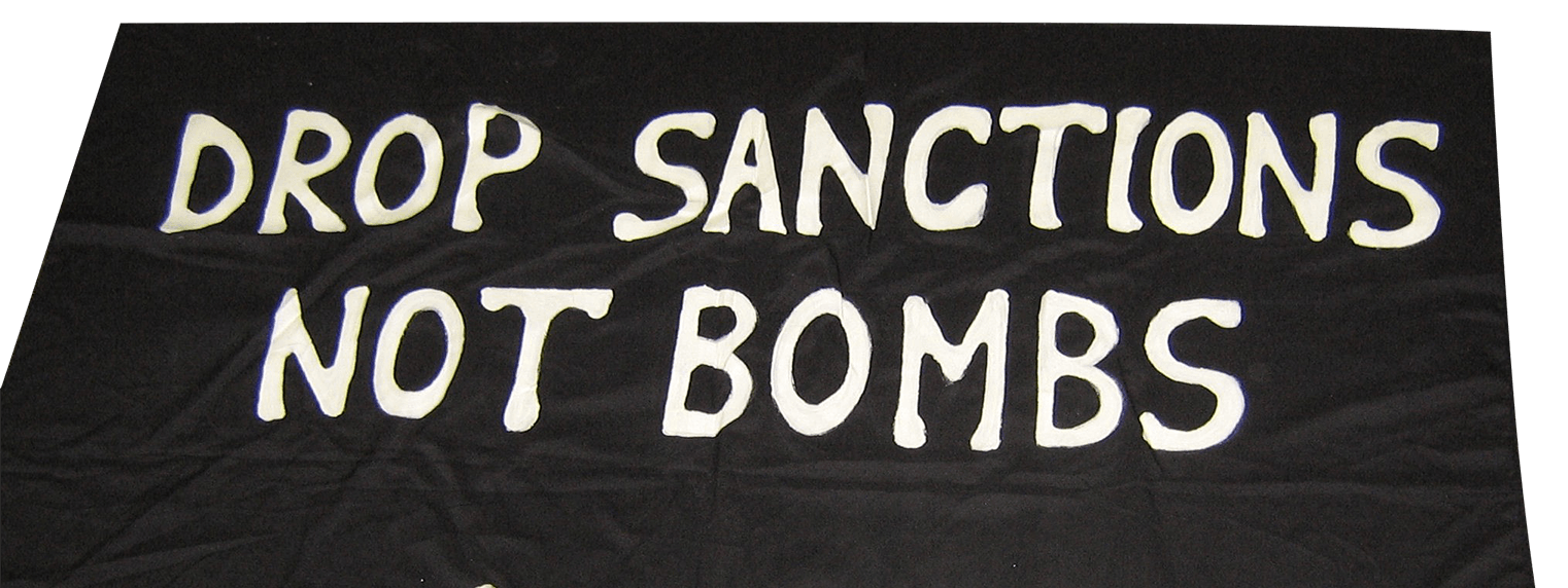 """A banner with the message """"Drop Sanctions Not Bombs""""."""