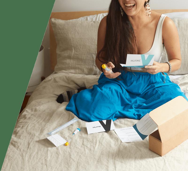 Women holding Ash kit laughing on bed