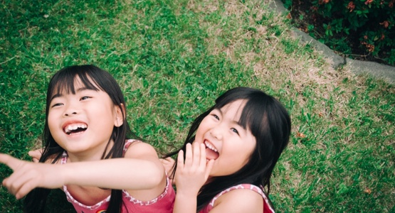 Two girls laughing outside on the grass
