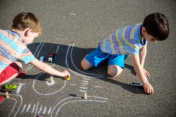 Kids playing with toy cards on the floor with the drawing of a roundabout.