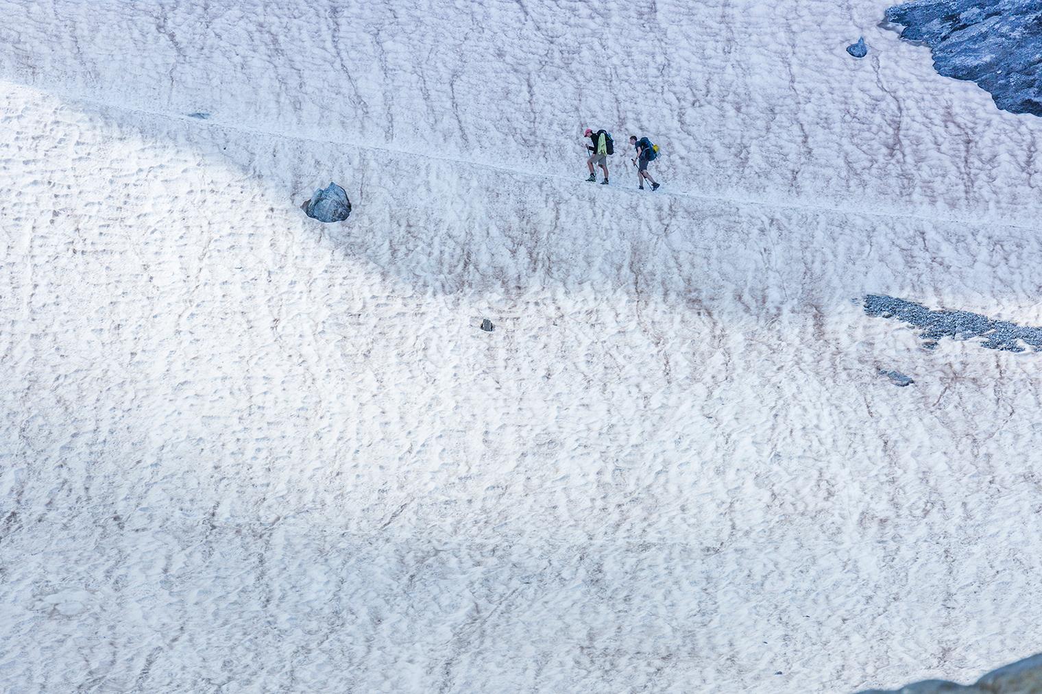 Dos ruteros cruzando una montaña nevada