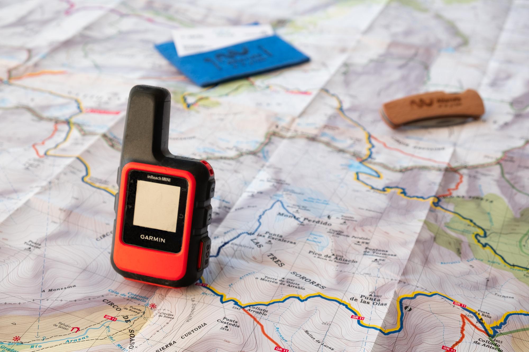 Dispositivo GPS Garmin inReach Mini y un mapa.