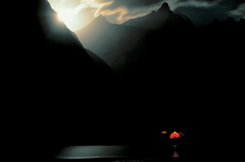 Tienda de campaña bajo un anochecer entre montañas