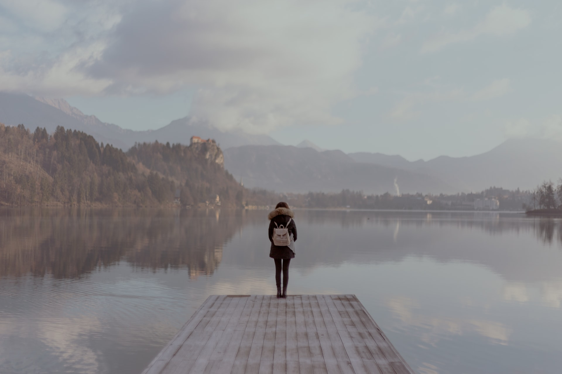 Ungraded image of a woman standing on a pier in front of a lake. Shot on Arri Alexa
