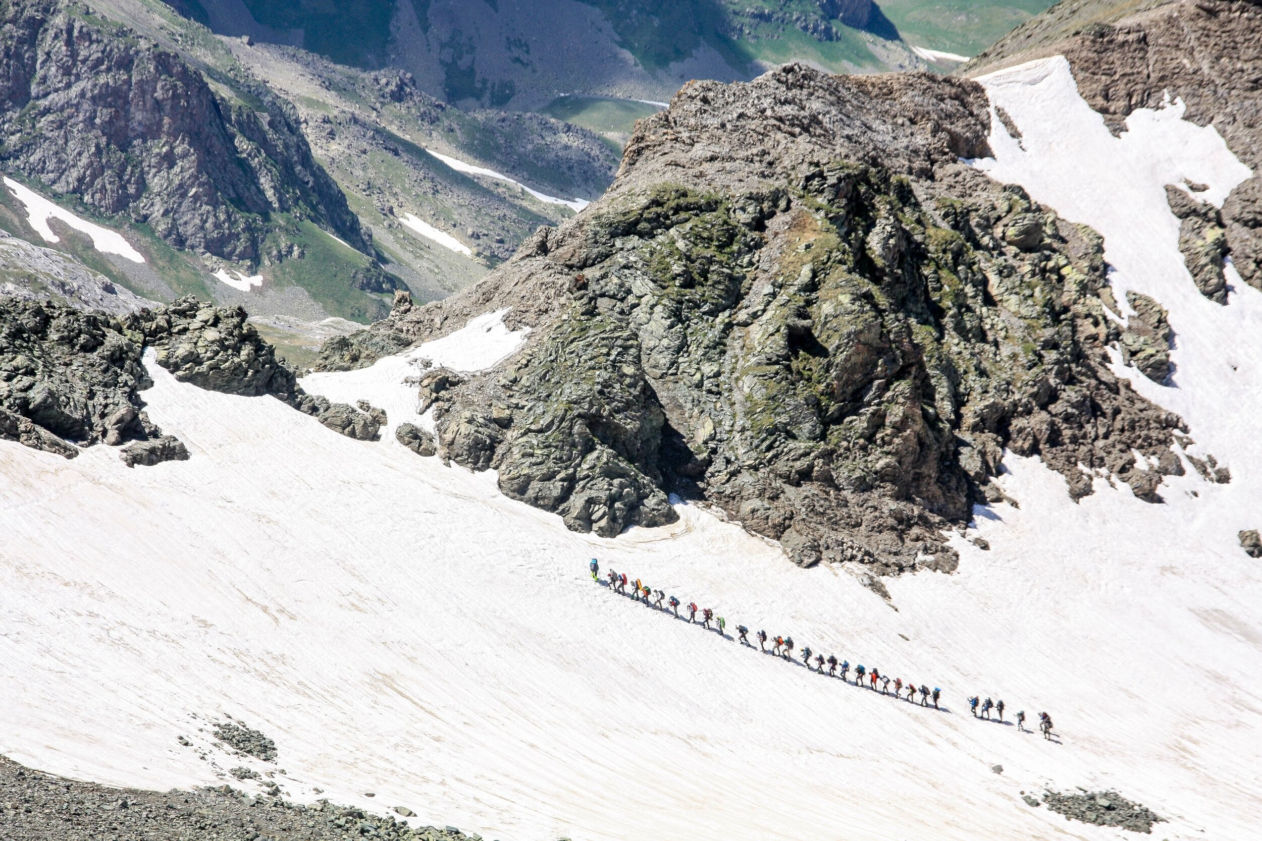 Snowy mountain with long line of hikers hiking up it