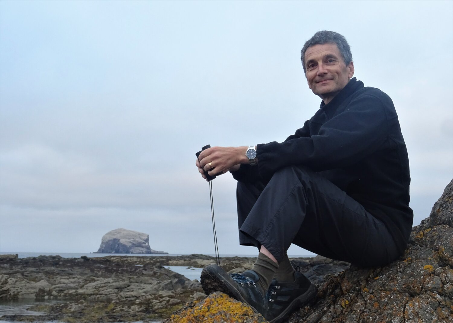 Neil Kitching, expert in regenerative agriculture and rewilding, sitting in front of the Bass Rock
