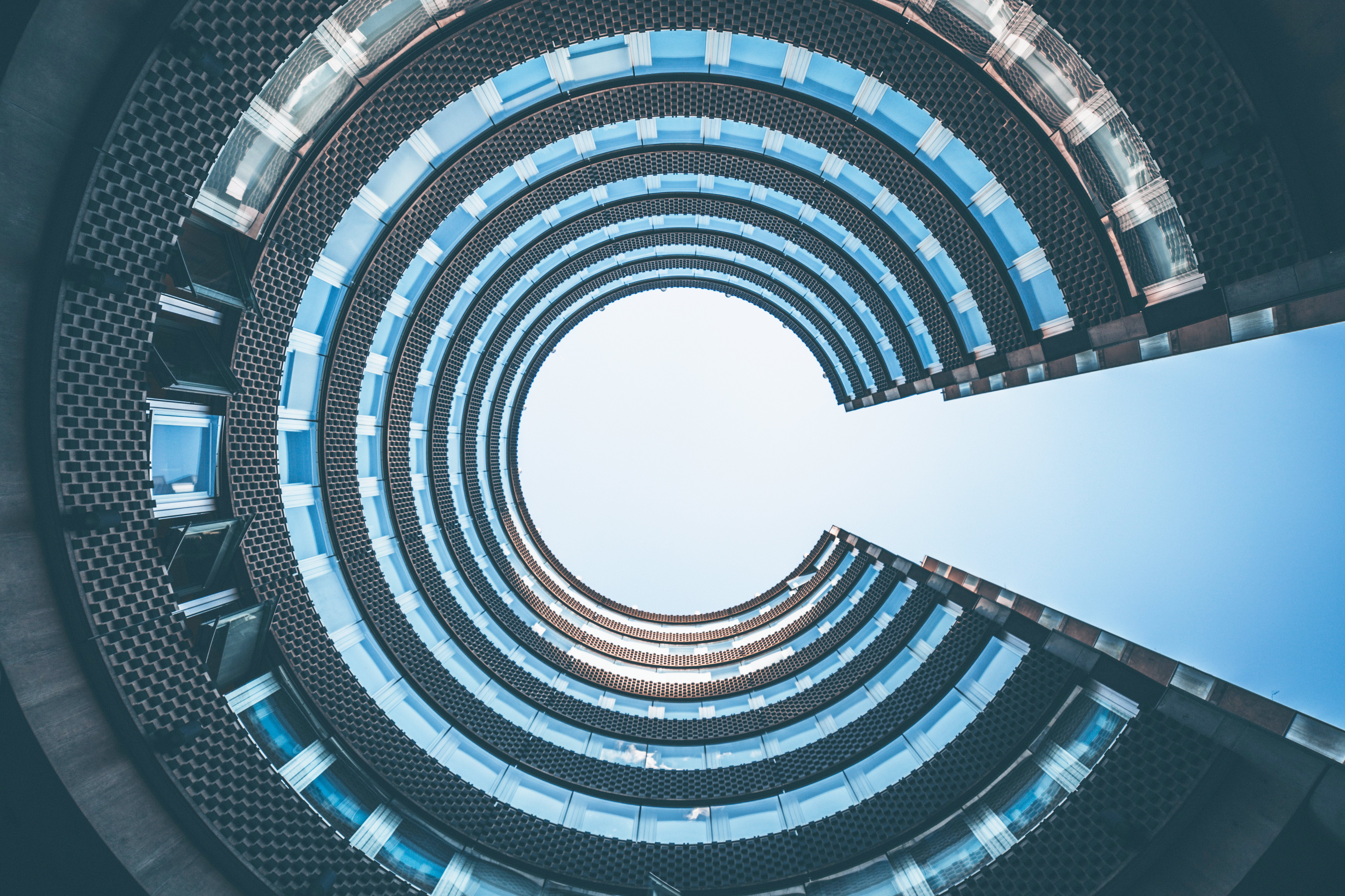 Worm's-eye view of a C-shaped glass building against a blue sky