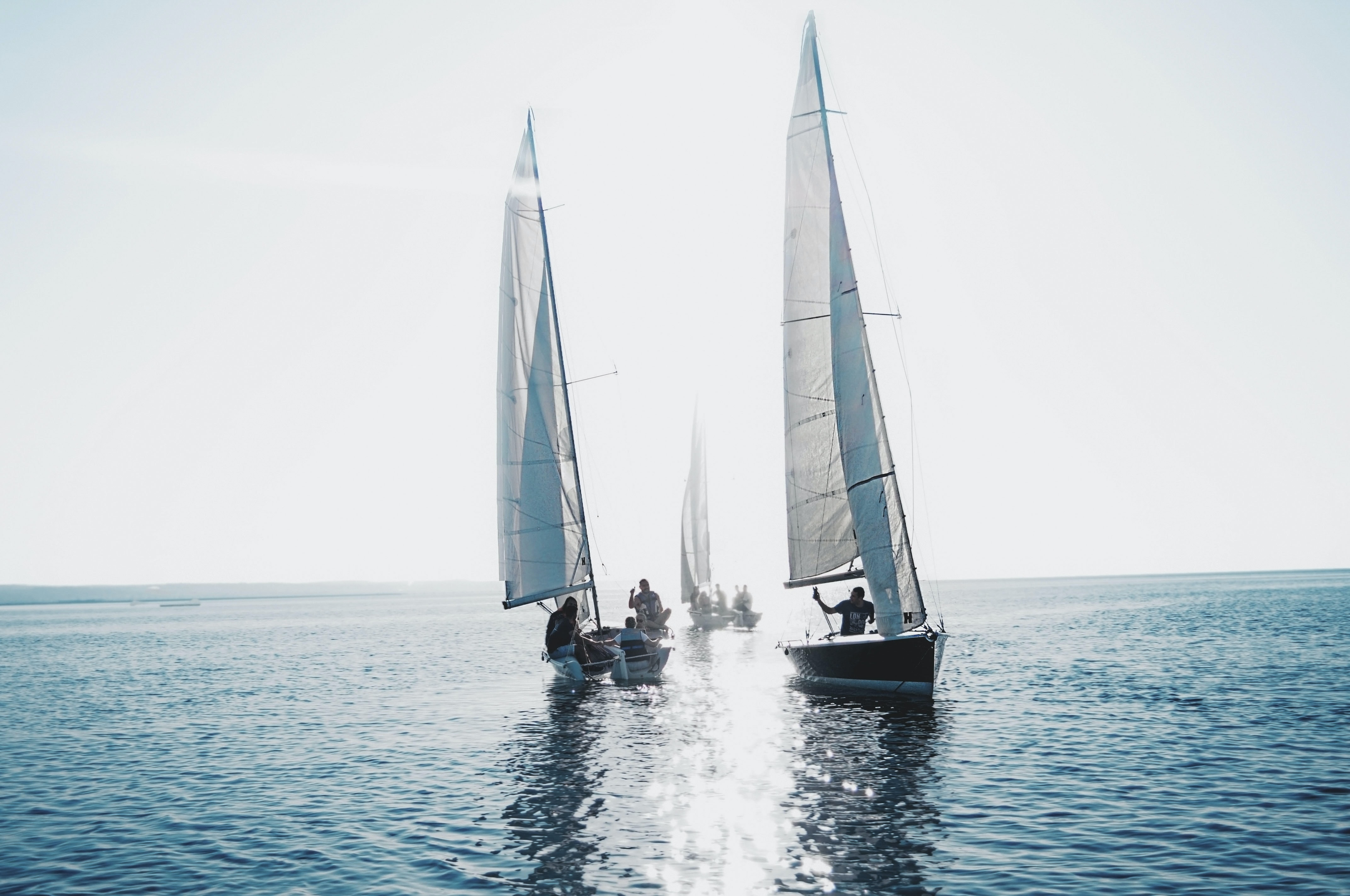 Two white sailboats side by side on a calm blue sea