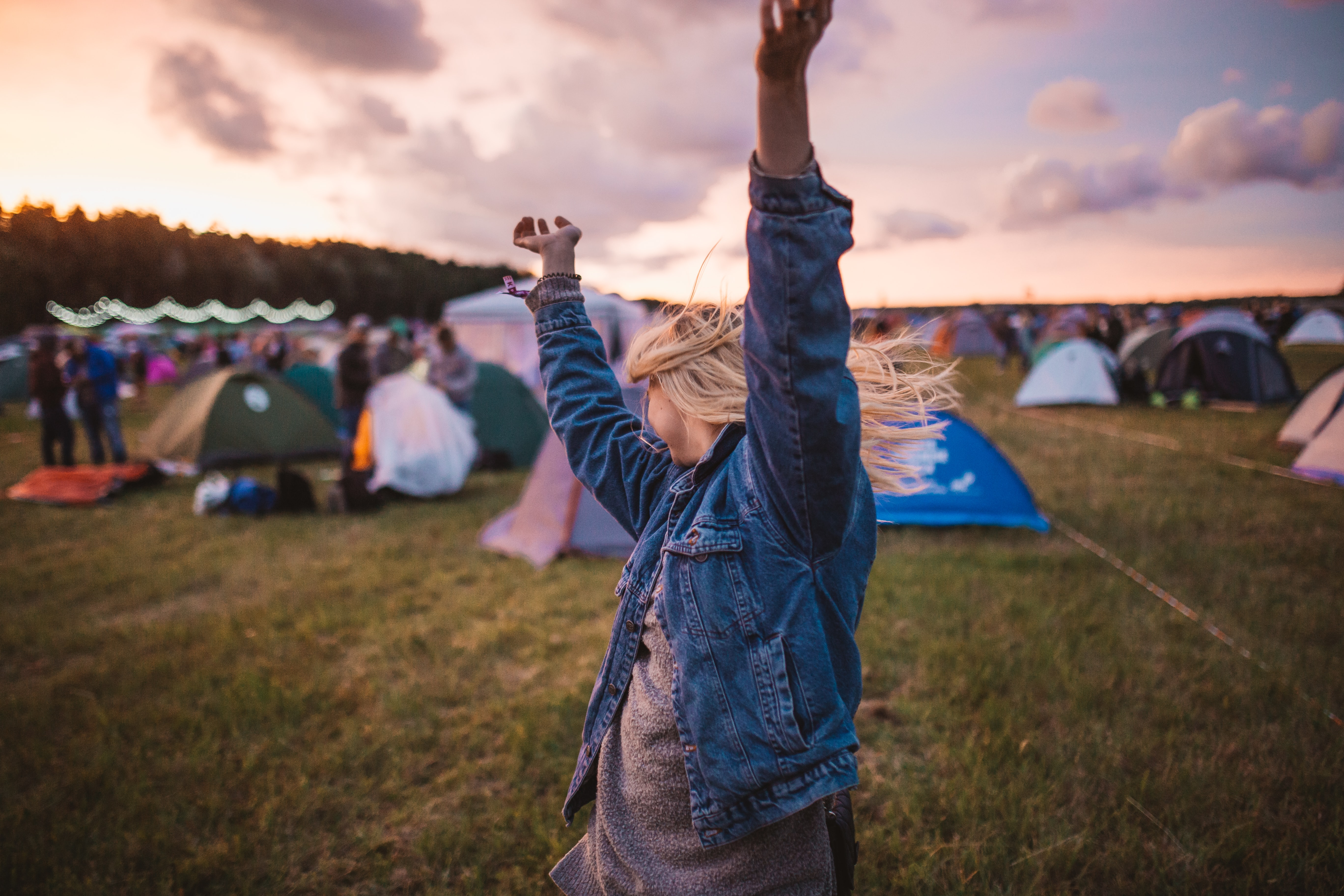 Young woman dances in field of tents