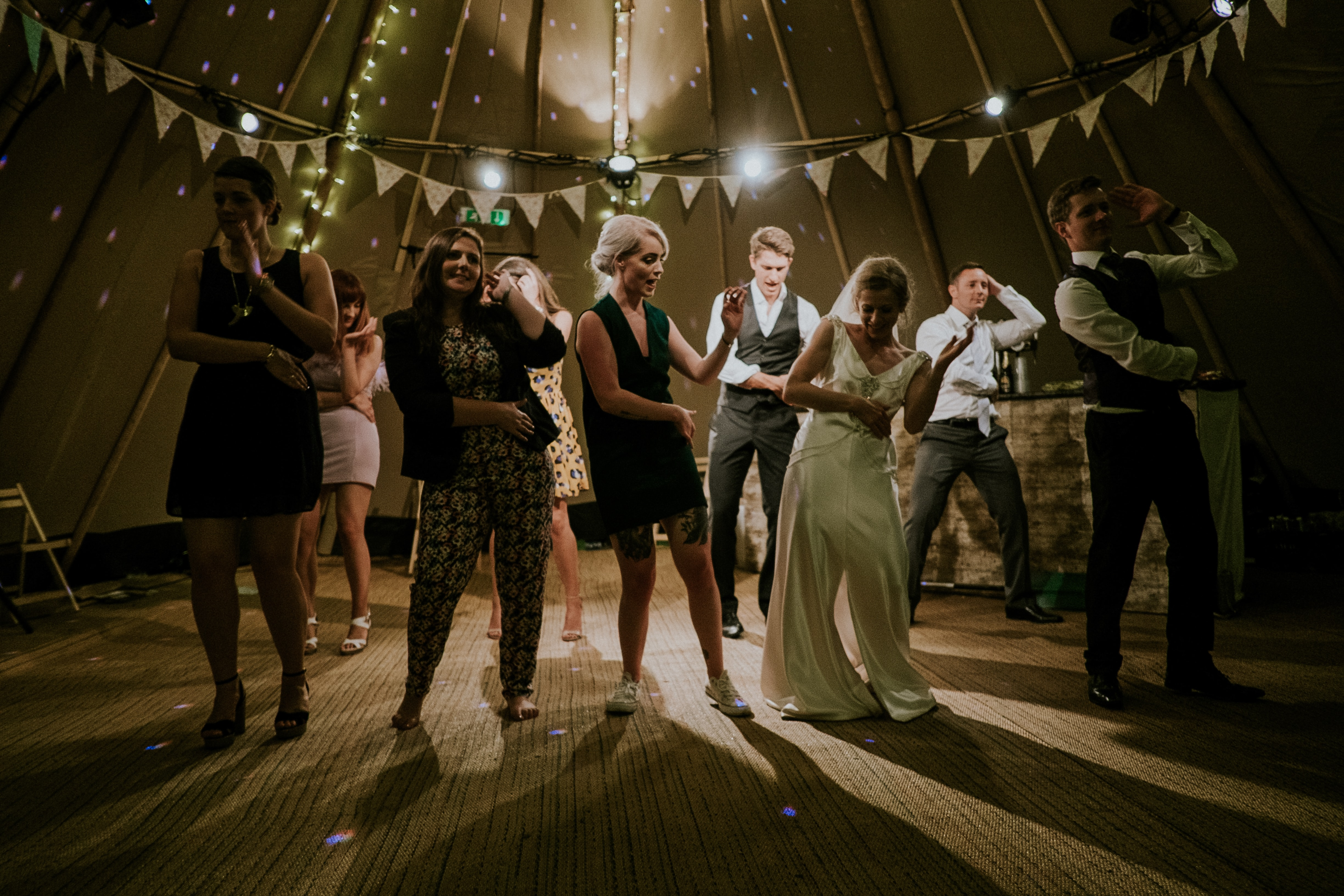 Group of wedding guests dance the macarena