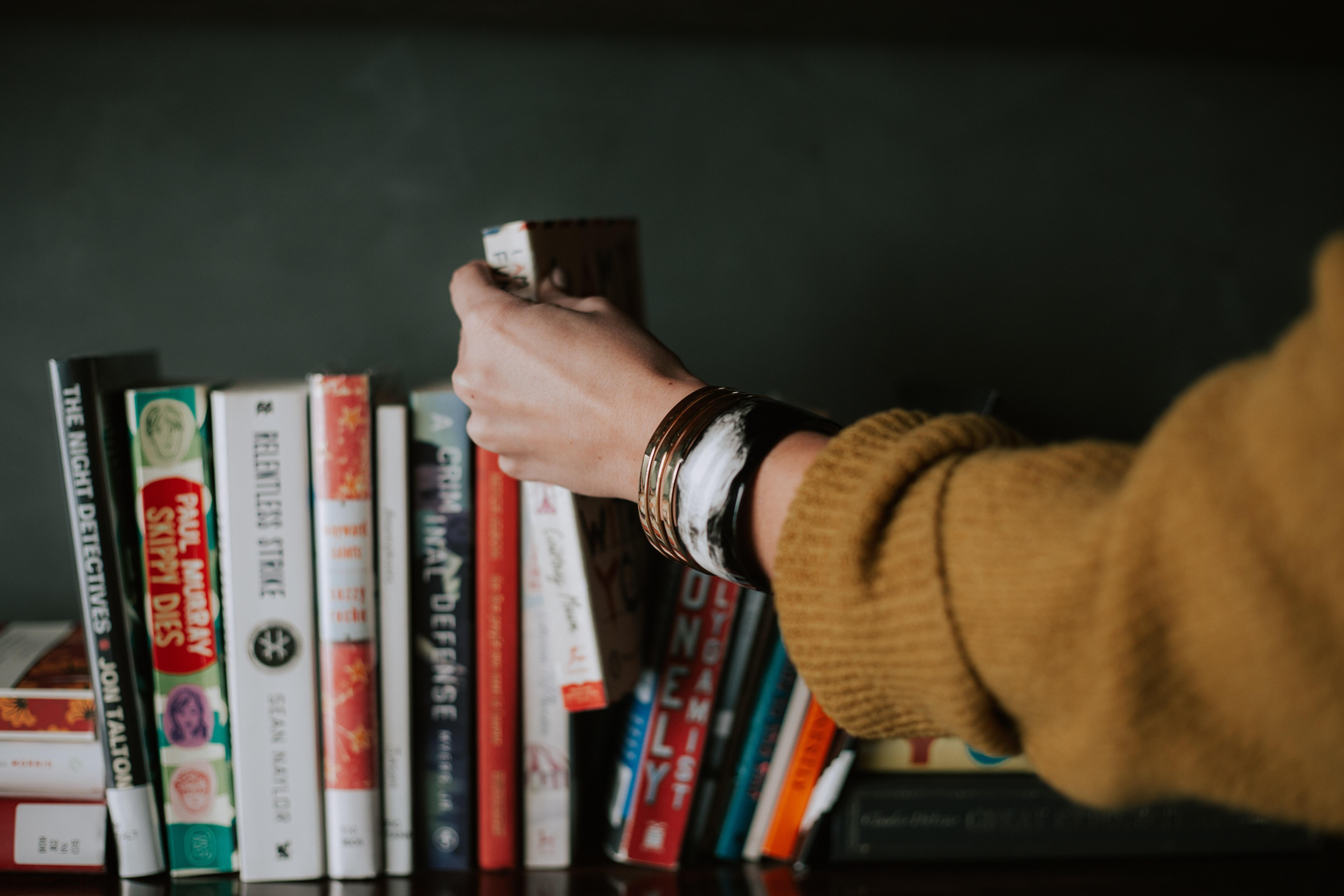 Arm taking a book off a shelf