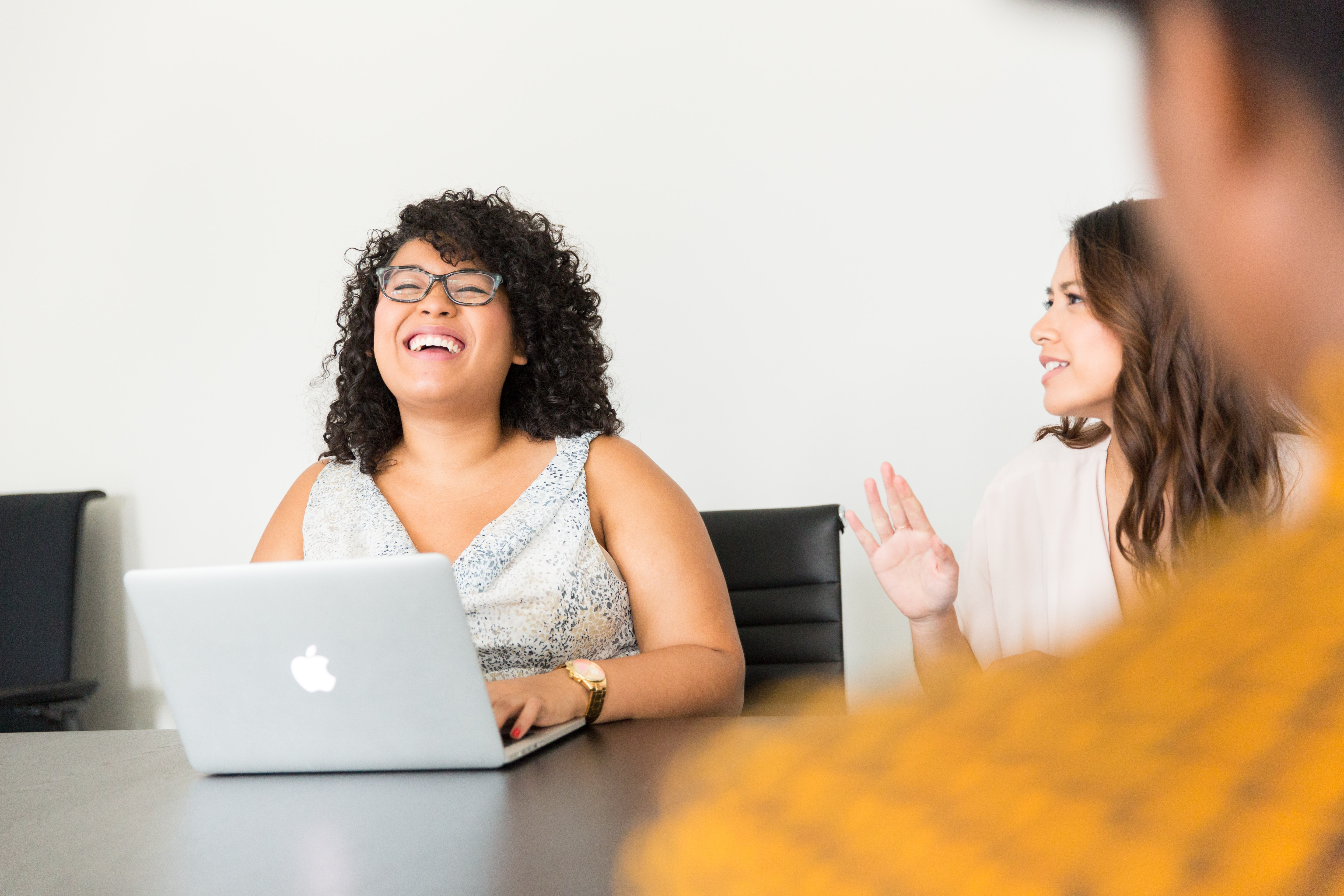 Woman with a laptop laughing in a meeting