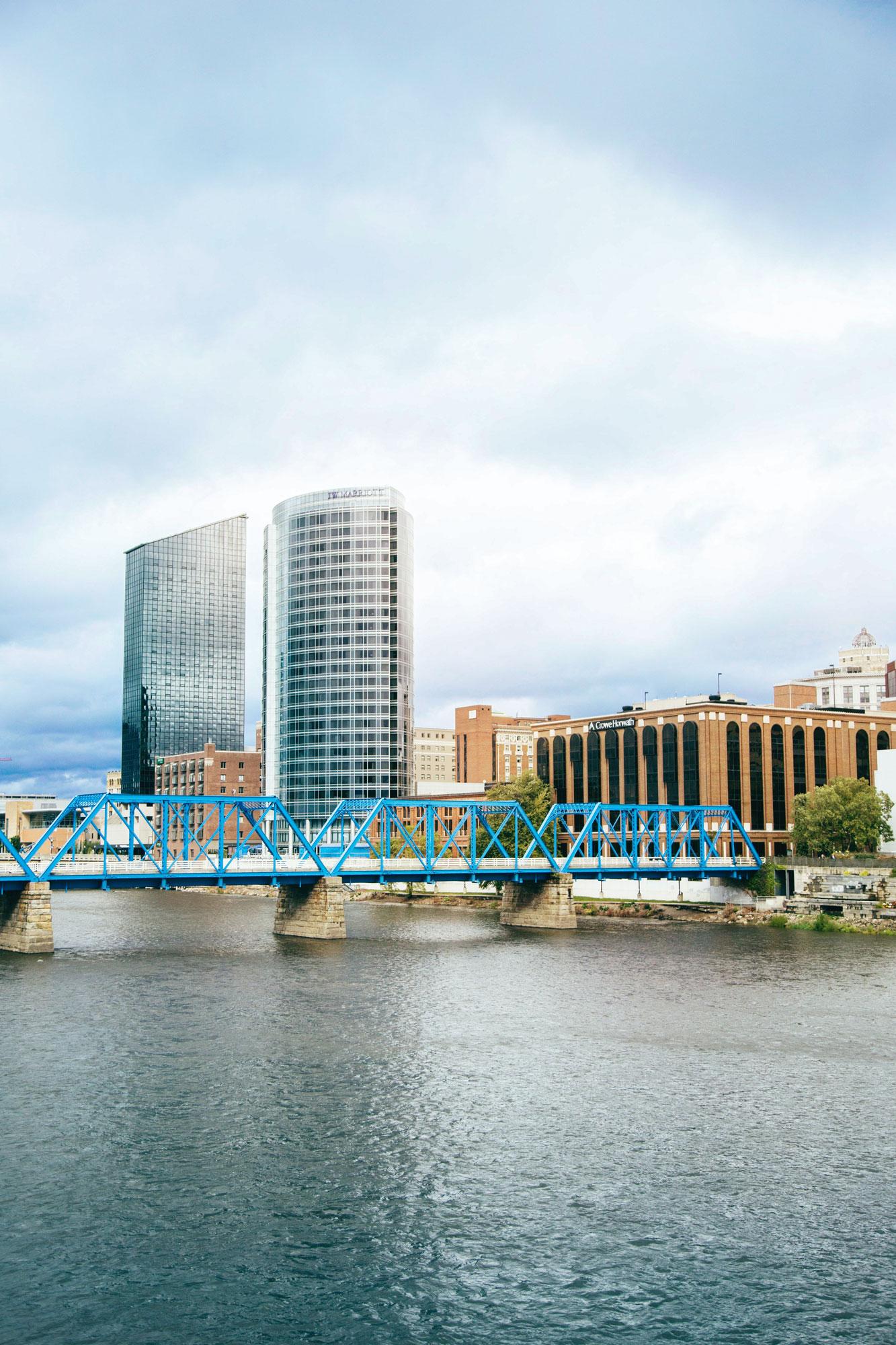 Blue bridge over river near city buildings during daytime photo. (Grand Rapids, Michigan)