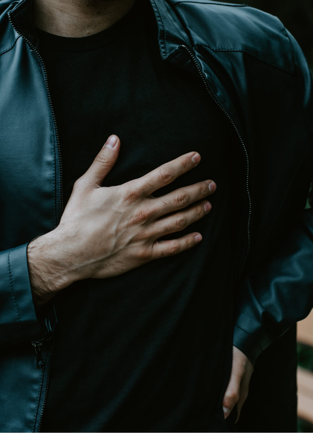 Man in a jacket with his hand on his chest
