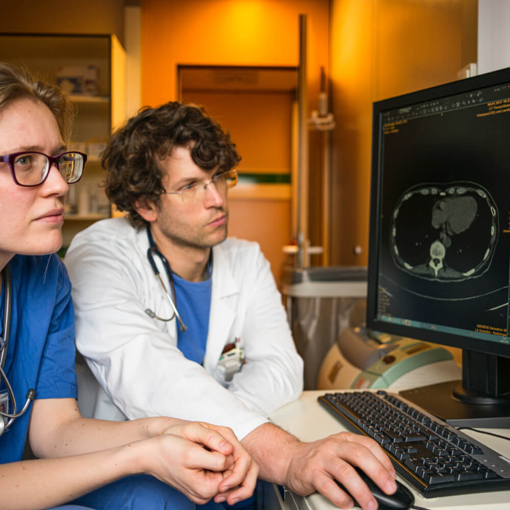 Two doctors looking at an MRI of a chest