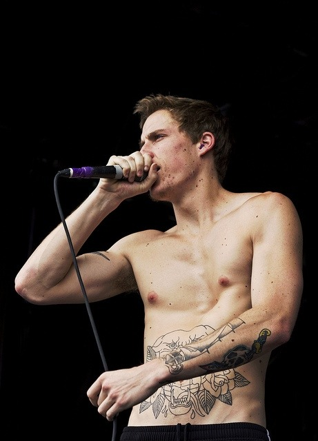 A man with pectus excavatum holding a microphone