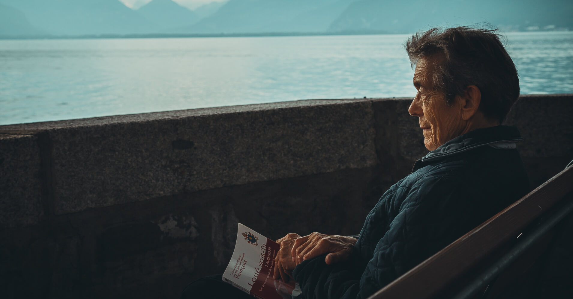 older man reading a book looking out at the sea