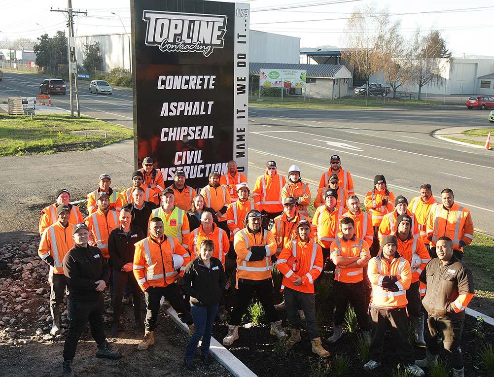 Topline team in front of sign